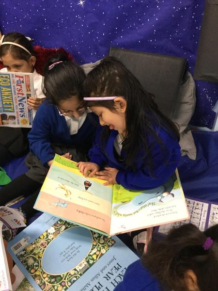 The girls enjoy reading a book together