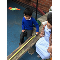 Hasnain measures the wooden plank.