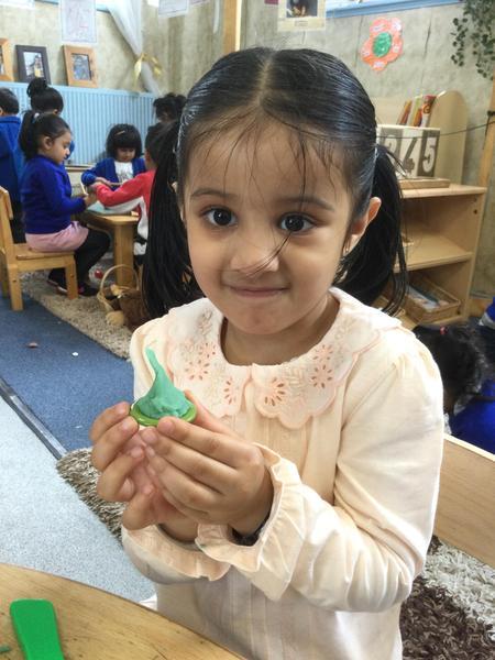 Amirah makes a mosque with playdough.