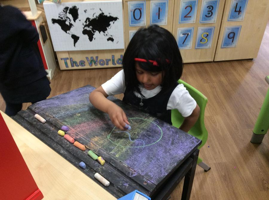 Hafsa drawing an egg on the chalk table.