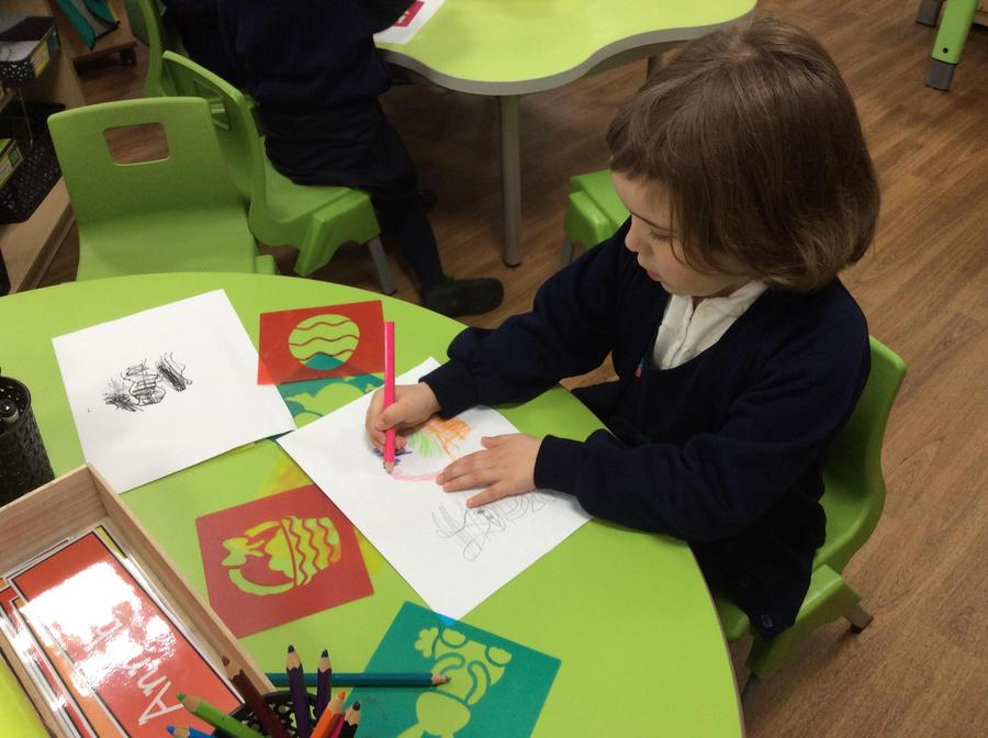 Harriet using the Easter stencils to make pictures.