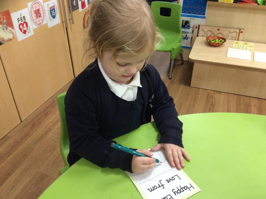 Imogen write her name in her card.