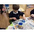 Christos chose blue to paint his milk bottle to make a vase.
