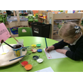 Imogen is writing 'Mummy' at the top of her portrait.
