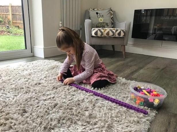 Measuring the rug using cubes.