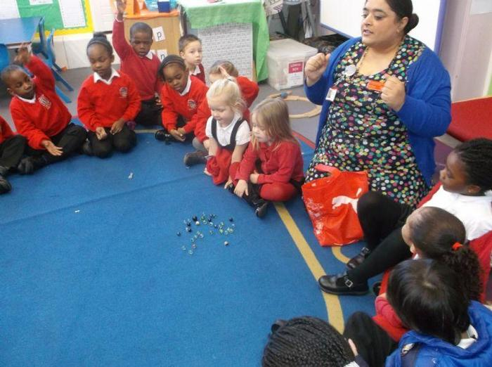 Mrs Guron shows the children how to play marbles