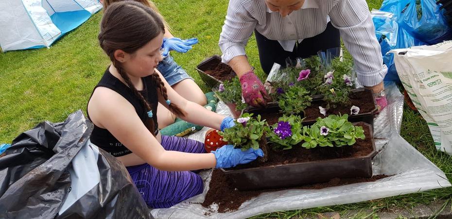 Zuzanna helping plant flowers