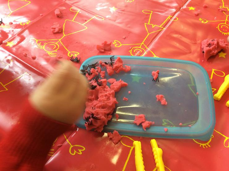Using tweezers to pinch the spiders from playdough