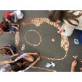 Year 6 children covering a number '90' in coins