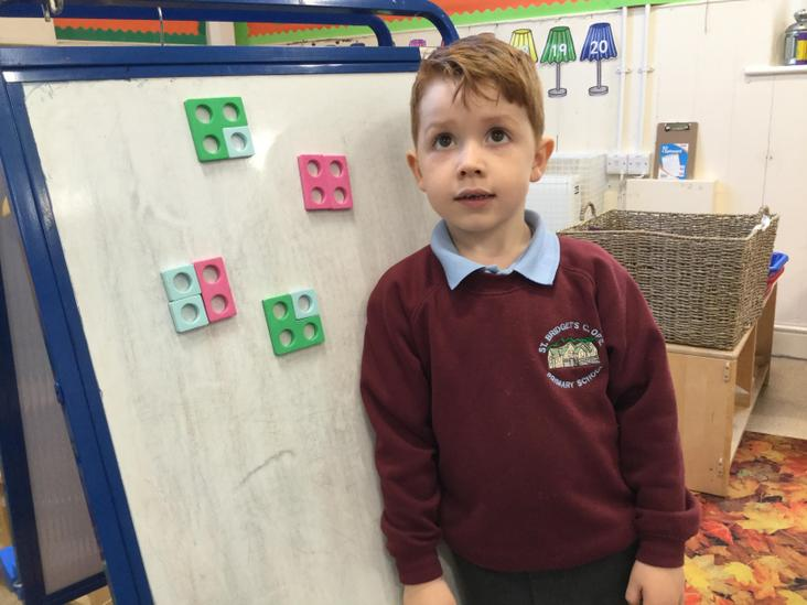 Harry using Numicon to explore the composition of four.