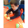 Using the scissors to cut the playdough