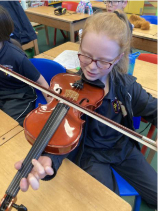 Practising holding a violin after our workshop with a violinist