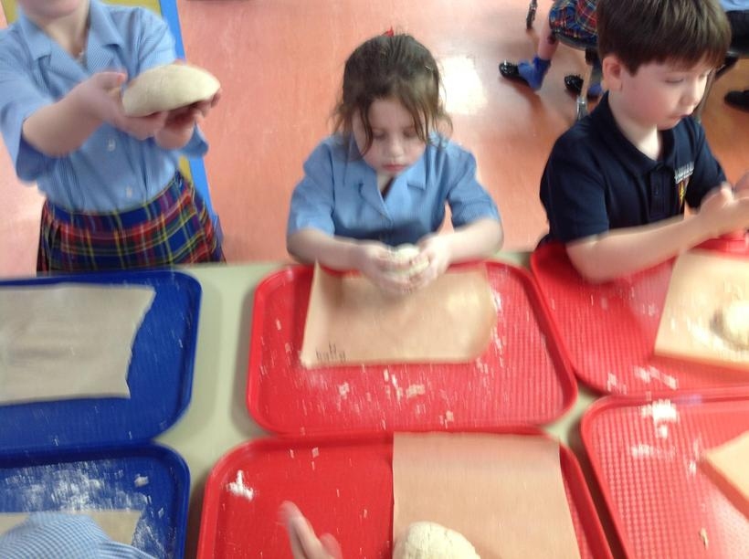 Shaping our pizza dough.
