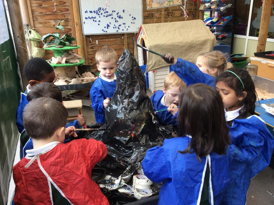 Children build a volcano for their role play area
