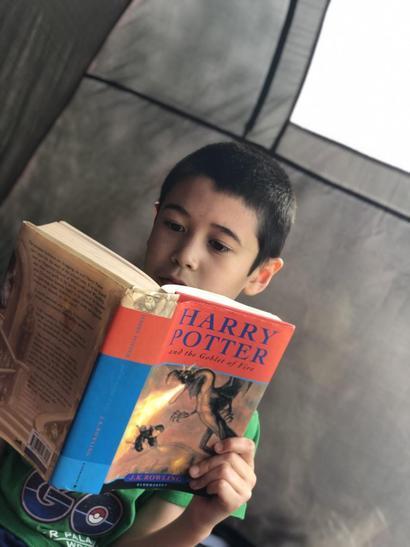 Callum reading his book in his tent