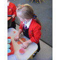 Rolling out the playdough to make cakes.