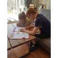 Joshua helping his sister with her Maths