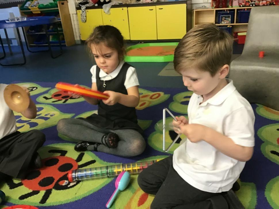 Early Years pupils experimenting with instruments