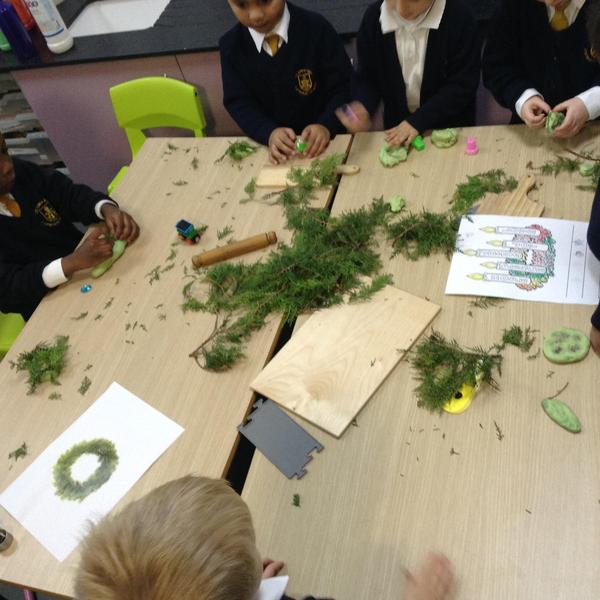 Using playdough and real leaves to create Advent Wreaths.