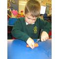 Carefully cutting carrots into sticks.