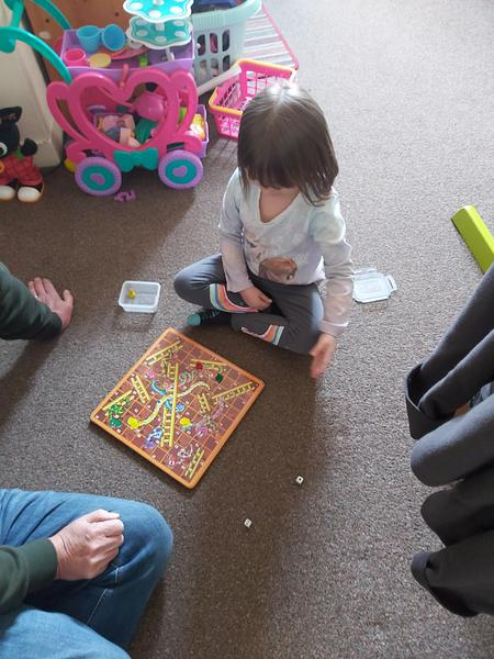 Lily-Mae playing a board game snakes and ladders
