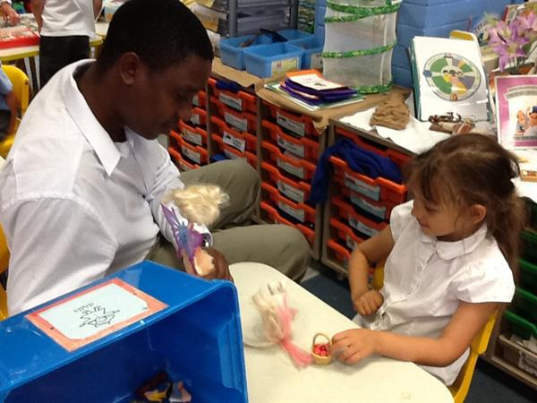 Obadiah playing with dolls in the Reception class