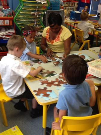 Grace helping out the children with their jigsaw.