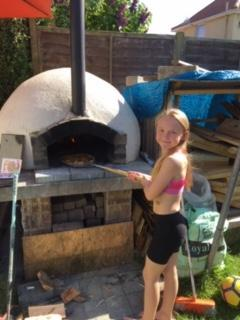 Marlie baking pizza in her pizza oven