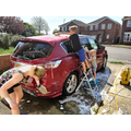 Andrew helping his family clean the car