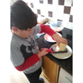 Ethan very carefully grating cheese for DnT