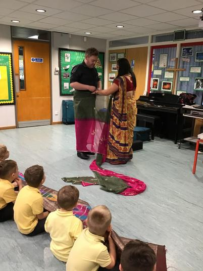 Mr Bell is learning how to put on a sari.