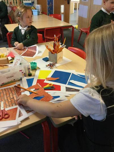 Cutting out shapes to make our houses!