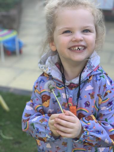 Felicity enjoying picking wishes (dandelion clocks)