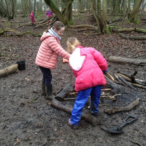 Georgina, Bryonny & Henry building the camp fire