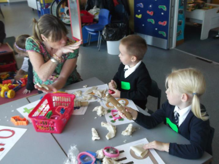 Miss Ottley plays with the playdough with us.