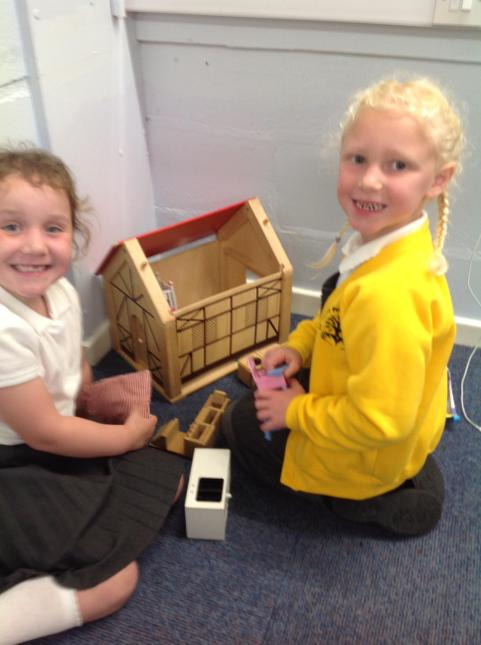 Happily playing with the dolls house.