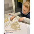 This young man is enjoying making tens and ones using beads!