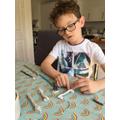 Benjamin making Stone Age weapons