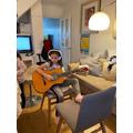 Mia practising her guitar playing