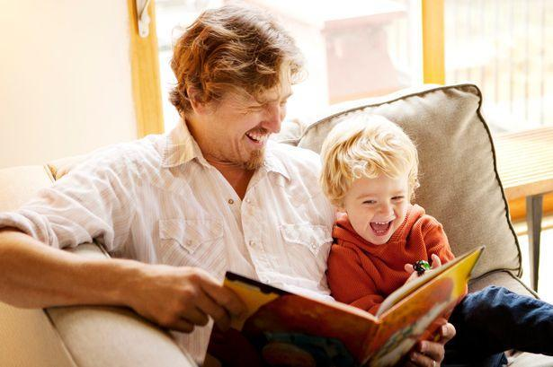 A man is sitting on a sofa with a boy. They are smiling whilst sharing a book together.