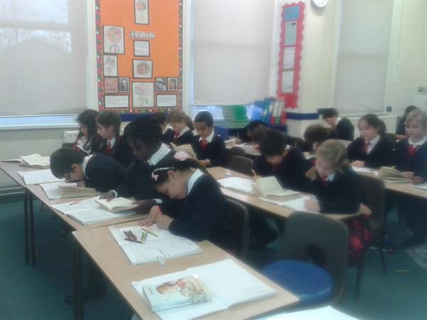 Pupils answering questions in their English books