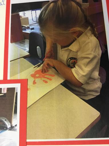Cutting out our printed handprints.