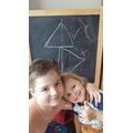 Thomas teaching his sister about symmetry.