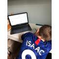 Isaac doing some learning using a laptop
