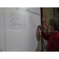 Showing how to solve a maths problem on the board.