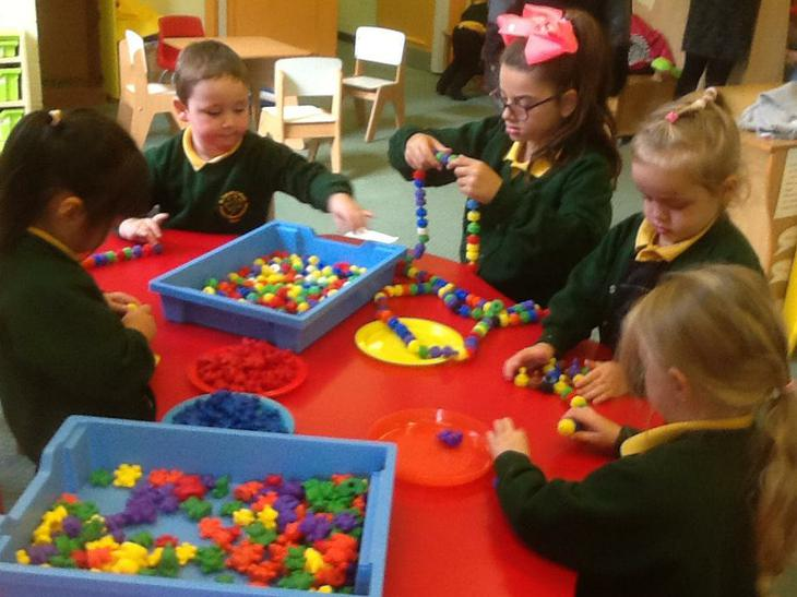 Learning to thread beads & sort colours.