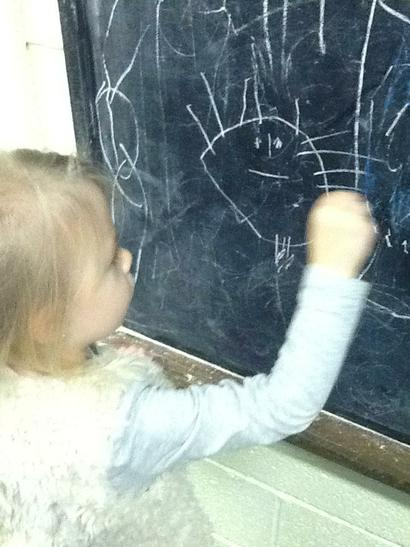 Chalking on the chalkboard.