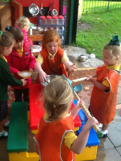 Working together to clean the Mud Kitchen!