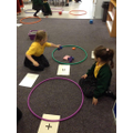 Year 1 use beanbags and hoops to add amounts