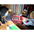 Sharing and taking turns with the dolls house.